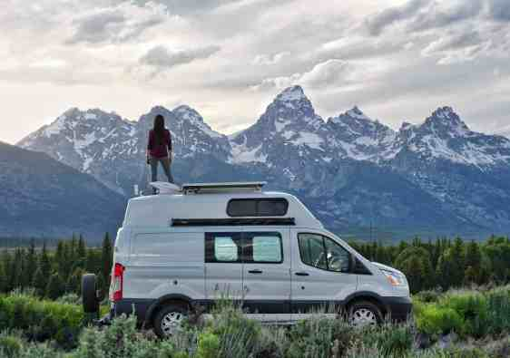 girl on van in front of grand teton mountains
