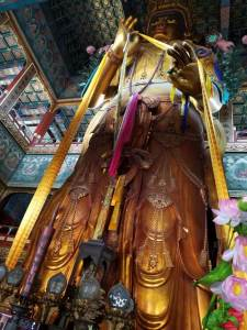 A golden Buddha photographed from below