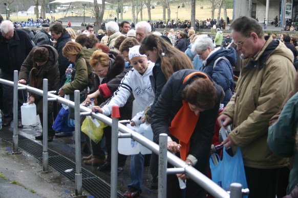 people getting holy water at Lourdes, France