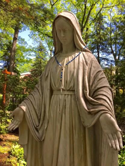 Virgin Mary statue wearing beaded rosary