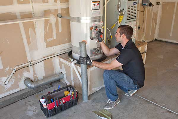 a plumber inspects a hot water heater that smells like nail polish