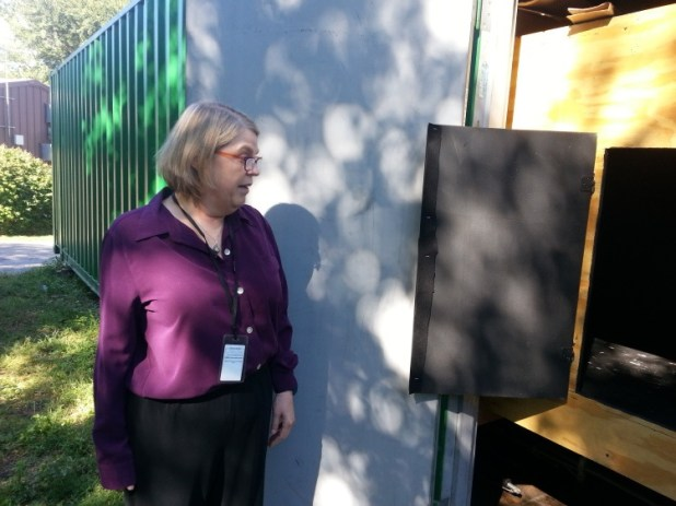 Christine Sheppard stands at the end of the bird tunnel. This experiment's goal is to identify which patterns of lines and dots in glass prevent birds from crashing, so safer windows can be designed for commercial development. (Jim Briggs)