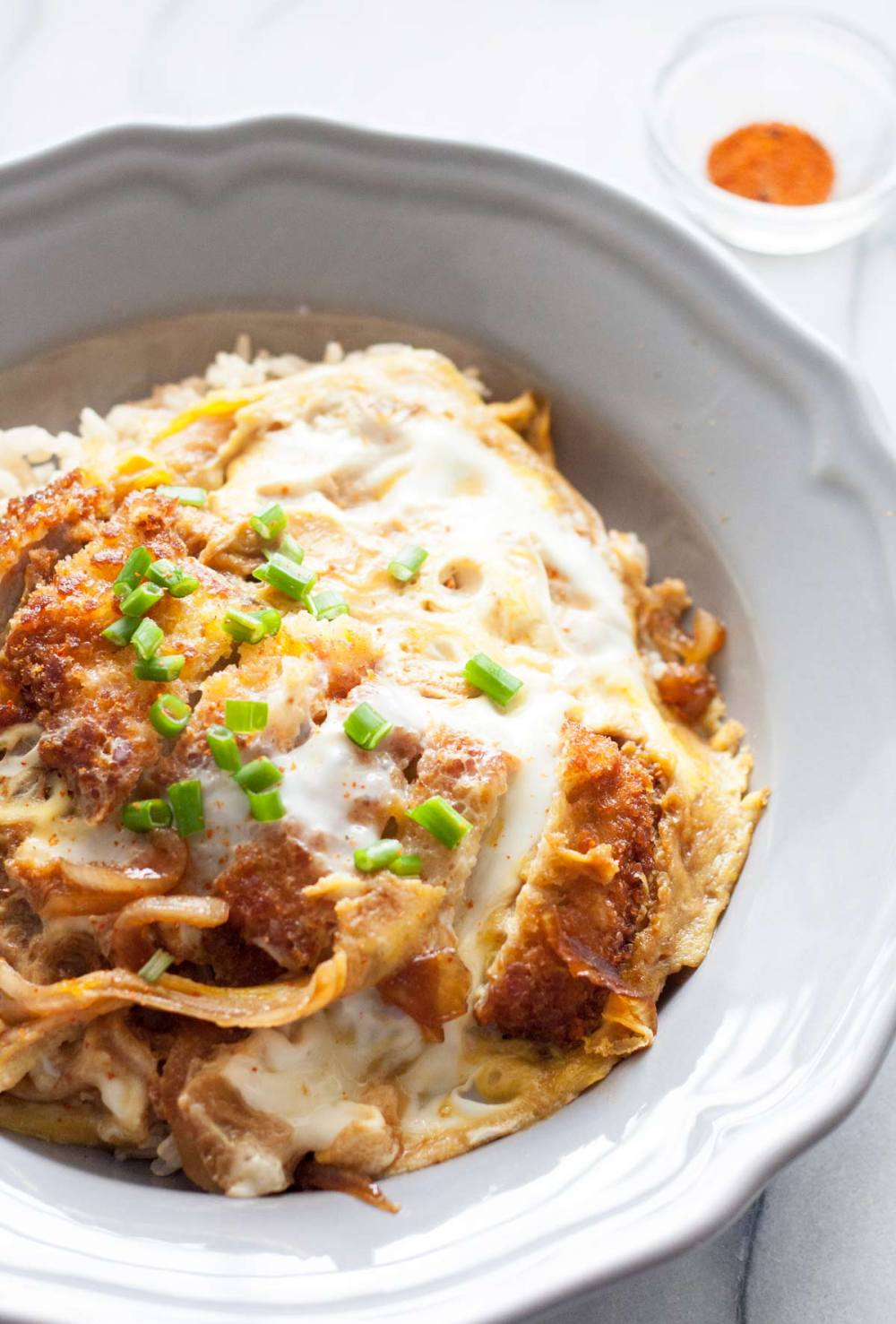 Katsudon is basically katsu (a pork chop breaded with panko and fried) paired with a slightly sweet mixture of egg and onion, laid over Japanese rice. | www.SpoonfulOfButter.com