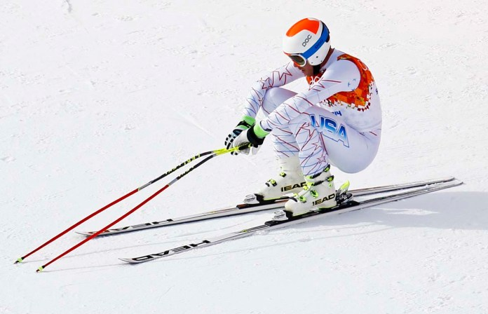 Miller of the U.S. squats after his men's alpine skiing downhill race during the 2014 Sochi Winter Olympics at the Rosa Khutor Alpine Center