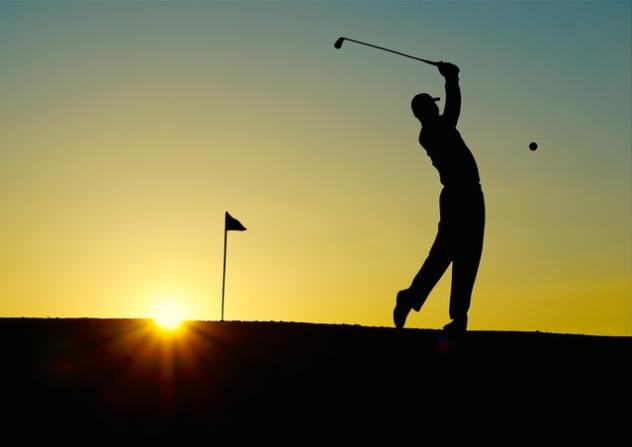 silouette of man playing golf