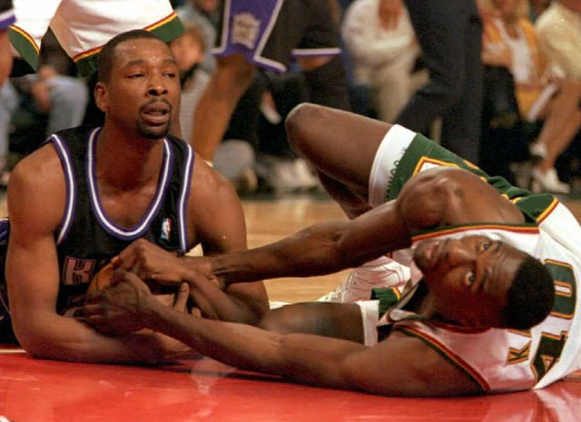 Seattle Supersonics Shawn Kemp and Lionel Simmons of the Sacramento Kings fight for the ball.