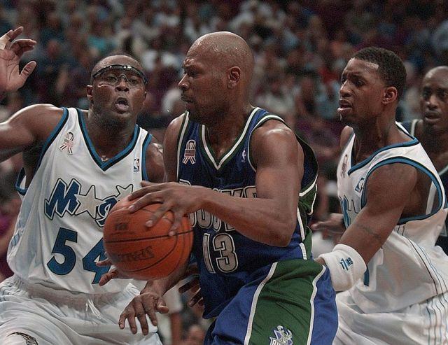 Milwaukee Bucks forward Glenn Robinson moves between Orlando Magic center Horace Grant and Magic guard Tracy McGrady.