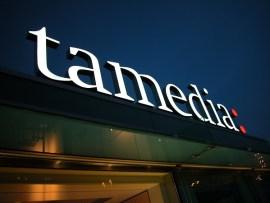 Das Tamedia-Logo auf dem Dach des Medienhauses Werd in der Dämmerung.