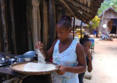 Una donna malgascia seleziona il riso