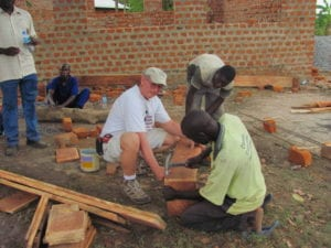 George Tockmakis, left, helps with a rebuilding project. Submitted photo