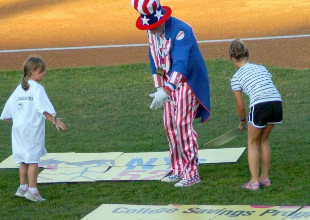 """""""Sammy"""" helps two young contestants during a between-innings contest. Rob Jonas/Spotlight"""