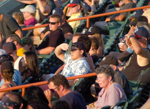 Fans along the first base line shield their eyes to watch the action during the Tri-City ValleyCats home game against the Connecticut Tigers. Rob Jonas/Spotlight