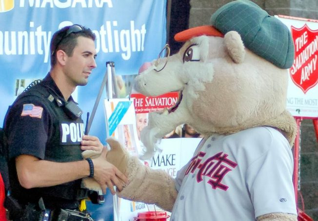 """""""Pappy Paw"""" shakes hands with a police officer. Rob Jonas/Spotlight"""