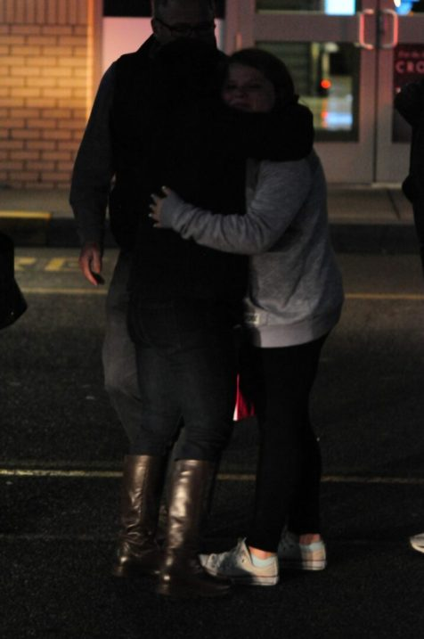 Two people comfort each other after being evacuated from Crossgates Mall Saturday evening after an alleged shooting took place there earlier that afternoon.