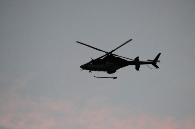 A helicopter flies over Crossgates Mall early Saturday evening as police continue their investigation into an alleged shooting which took place earlier in the afternoon.
