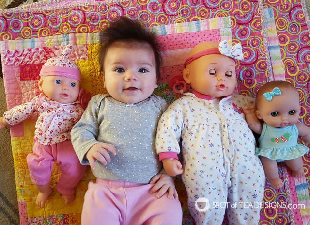 Real baby girl and her collection of baby girl dolls | spotofteadesigns.com
