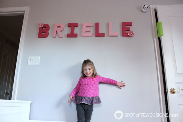 Brielle and the yard wrapped letters hung in her pink and yellow toddler bedroom | spotofteadesigns.com