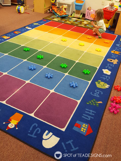 Ways to practice color recognition with toddlers - sorting on a colorful rug | spotofteadesigns.com