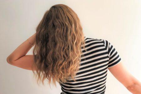 Femme aux cheveux blonds, vagués et en mouvement, de dos, et portant un t-shirt rayé noir et blanc.