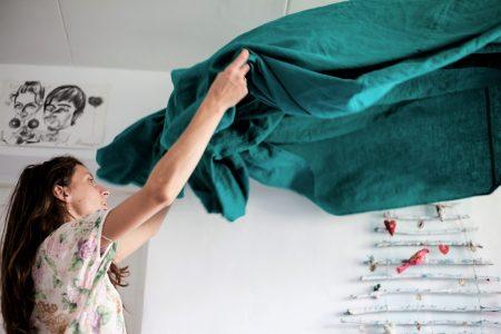"""Femme brune secouant un drap de couleur verte, pour imager la thématique """"grand ménage du printemps"""", propreté, fraîcheur."""