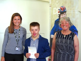Matthew Simmons, 15, receiving his certificate from Alice McLinden and Susan Davis