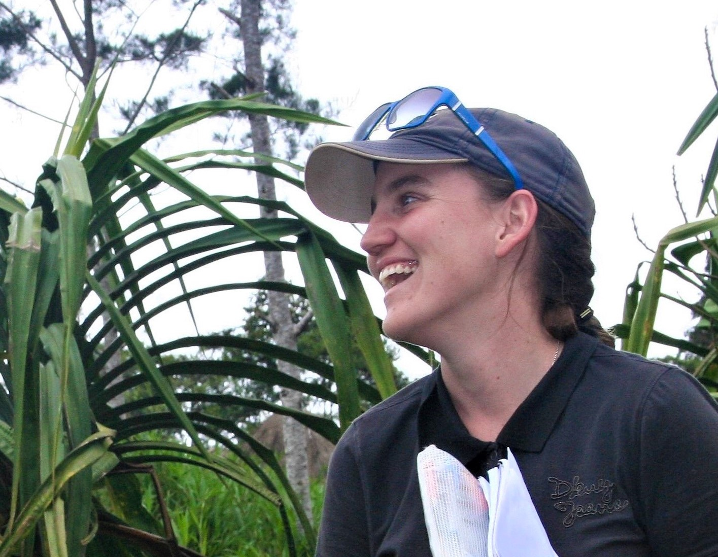 Rachel is pictured holding a notebook of fieldnotes. She is wearing a baseball cap and sunglasses and is laughing with an interviewee (who is just out of frame).