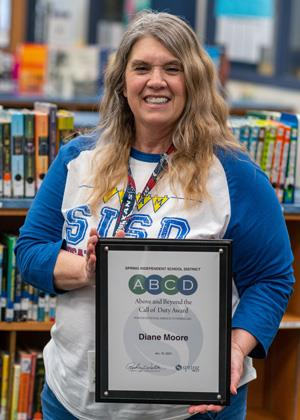 Hirsch Elementary School second-grade teacher Diane Moore holds the ABCD award honoring her for coming to the aid of a choking student