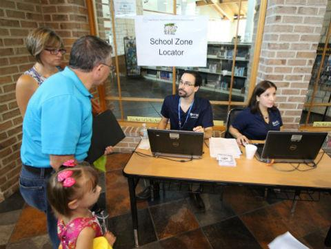 A Spring family consults with district representatives assigned to verify school attendance zones at last year's expo