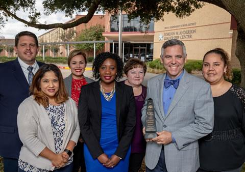 Spring ISD Procurement Services team members gather outside the district's headquarters with the department's 2018 Achievement of Excellence in Procurement Award