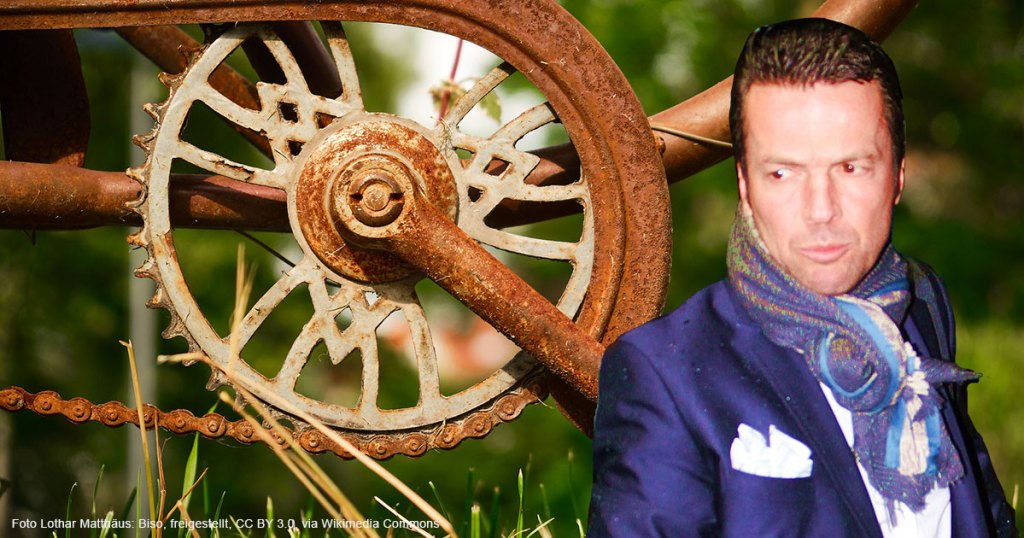 Lothar Matthäus mit lila Anzug blickt auf eine rostige Fahrradkette
