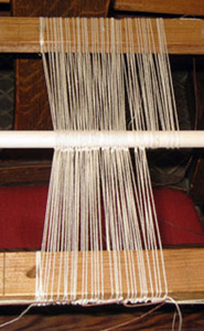 "Heddle construction required ""knit heddles."" The process involves knots and loops. It's done in two steps: first one side, and then the heddle eye, and then the other side."