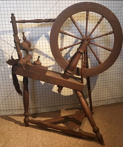 American style horizontal treadle wheel with mother-of-all set into a block of wood on top of table.