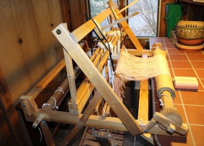 Two-legged loom attached to tile worktable; swinging beater, 4-shafts, warp beam with wooden ratchet.