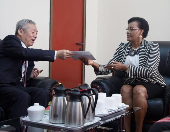 Ambassador of People?s Republic of China to Rwanda Shen Yongxiang( L) gives a parcel containing Merry Christmas message to Speaker of Parliament Mukabalisa Donatille