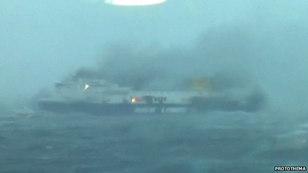 Pictures show thick black smoke engulfing the ship in rough seas