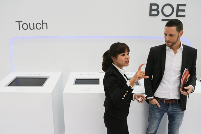 A visitor listens to introductions at BOE's stand of 2015 CeBIT Technology Trade fair in Hanover, Germany, on March 16, 2015. Top IT business fair CeBIT 2015, which features a strong Chinese presence this year, opened on Sunday in Hanover. (Xinhua/Zhang Fan)
