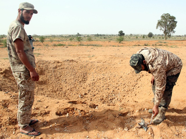 A Libya Dawn fighter picks up a shrapnel in a crater left by an air raid in the Tarhuna area, 80 km southeast of Tripoli, Libya, on March 23, 2015. Libyan national army's warplanes launched an airstrike on Tarhuna, attempting to pound the stronghold of Libya Dawn. (Xinhua/Hamza Turkia)