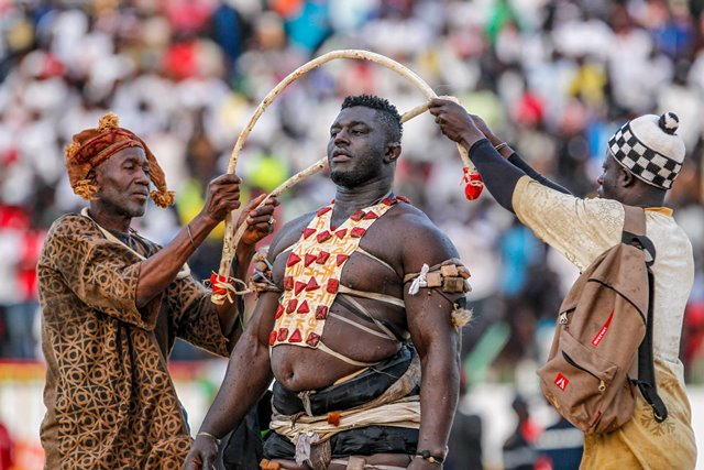 "Balla Gaye 2 (C) performs mysterious ritual before the Senegalese traditional wrestling match ""Le Choc"" at Demba Diop Stadium, Dakar, capital of Senegal, April 5, 2015. Thousands of audience have watched the biggest match here on Sunday at the beginning of the wrestling season with the most famous wrestlers Balla Gaye 2 and Eumeu Sene competing. Eumeu Sene won the match at last. (Xinhua/Li Jing)"
