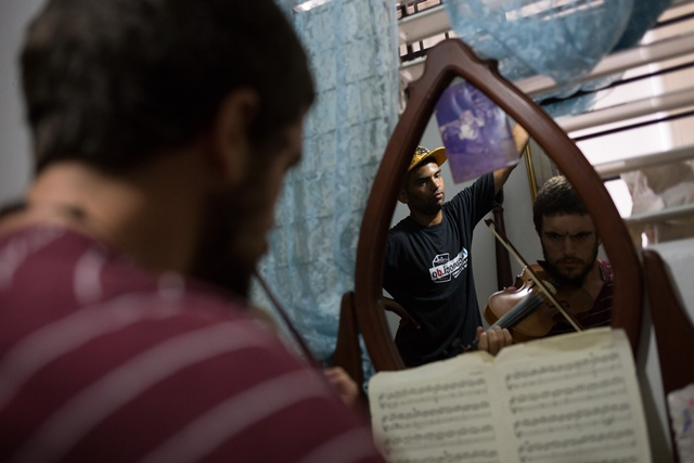 Image taken on April 3, 2015 shows Felix Cepeda (L), son of farmers of La Vega Province who migrated searching for better economic conditions, watches his friend David Janicki (R) playing his violin in Santo Domingo, Dominican Republic. Felix Cepeda has become a social worker for 15 years in Dominican Republic. During the Holy Week, Felix Cepeda and his friend David Janicki attended religious celebrations and visited people in povery, with whom they share water, cookies and talks, bringing them emotional support. (Xinhua/Fran Afonso) (rtg)