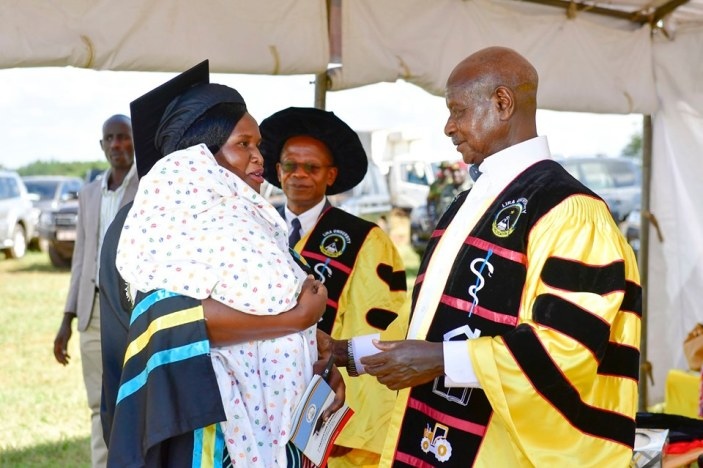 Museveni interacts with one of the graduands as Min. for Higher Education J C Miyingo looks on