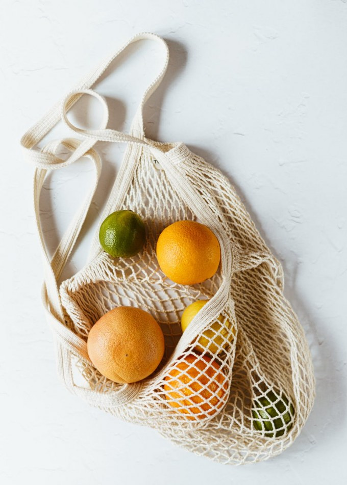 assorted citrus fruits in cotton sack on white surface