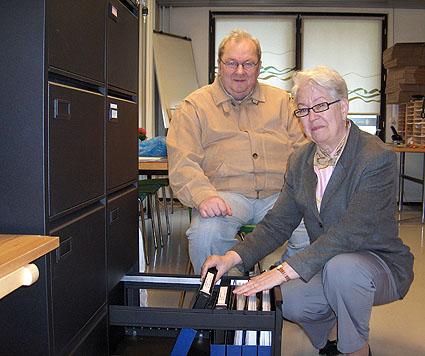 Ritva ja Kille laittavat kansioita arkistokaappiin.