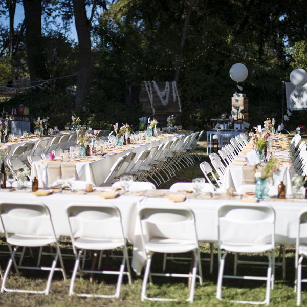 Basic white folding chairs with banquet tables in an outdoor setting event