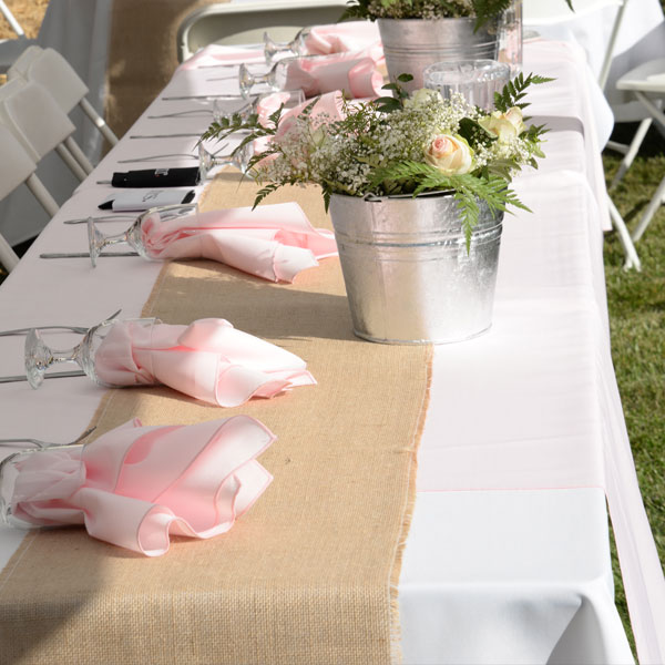 rectangular table in use at an event - with glassware holding the linen napkins