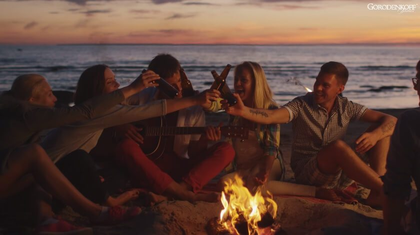ljudi sjede oko vatre na plaži