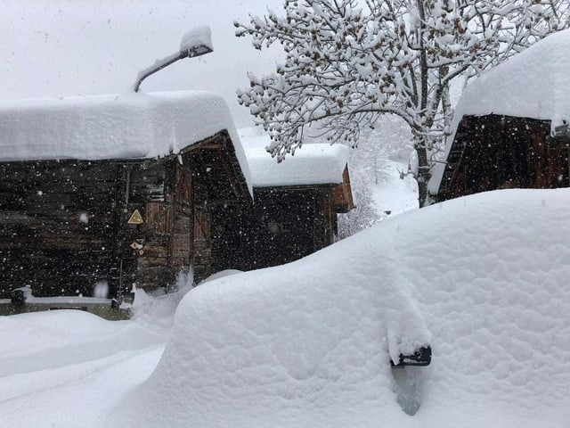 Snow-covered car in Goms