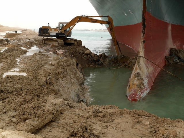 This picture went around the world and caused amusement: A single excavator tries to dig the huge ship a little bit free.
