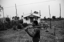 A Muria man carries water past a church in Ramachandrapuram, one of the early settlements in the region.