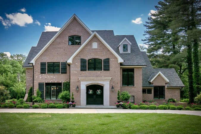 Custom corner lot home with brick exterior and cut stone entry surround