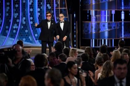 """Aplaudidos de pé, Elton John e Bernie Taupin apresentaram o clipe de """"Rocketman"""", longa que lhes rendeu o Globo de Ouro de melhor canção por """"I'm Gonna Love Me Again"""" (Foto: Divulgação / Crédito: HFPA Photographer)."""